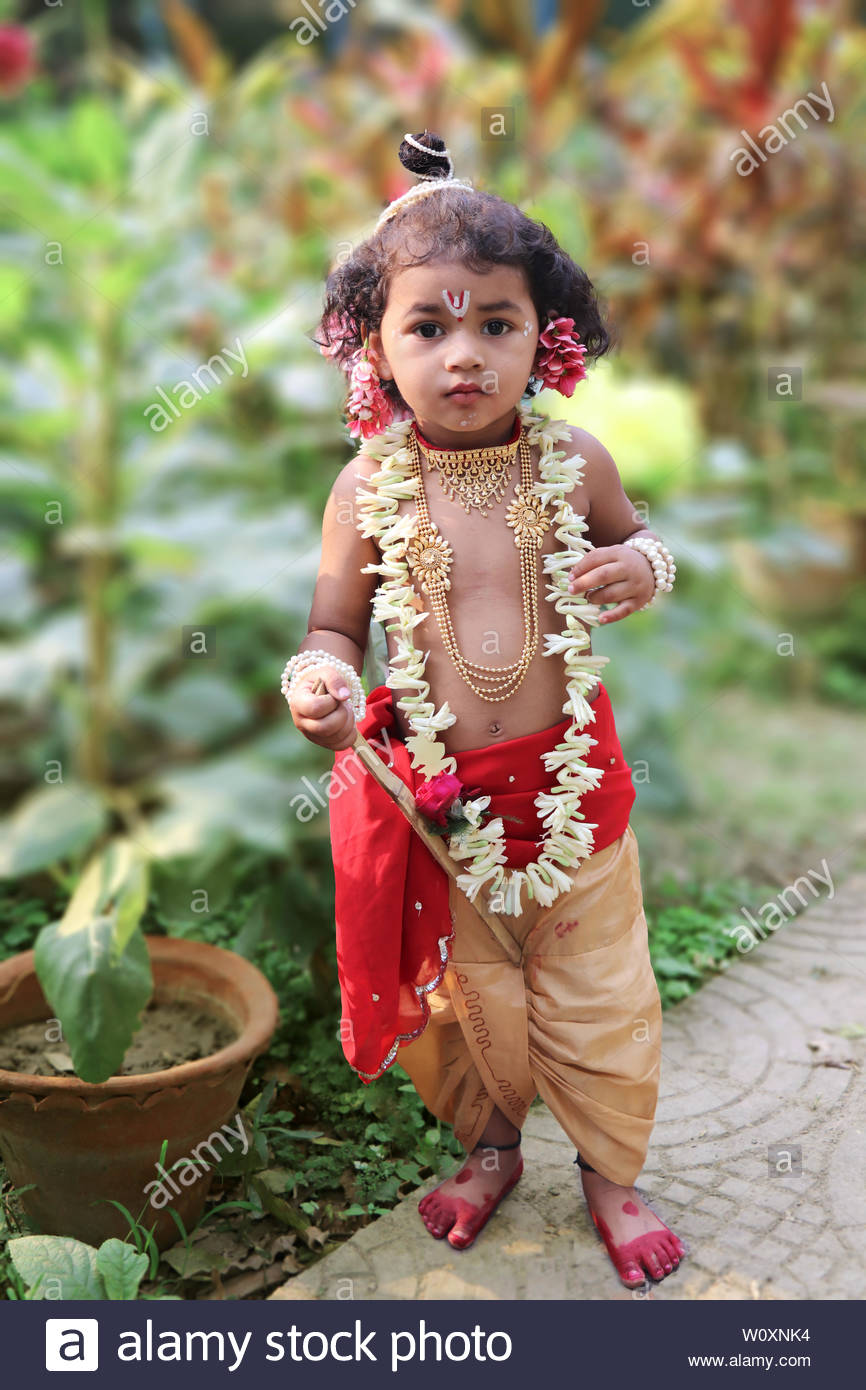 adorable baby boy dressed up as little krishna and playing with wooden flute in garden on the occasion of krishna janmastami W0XNK4