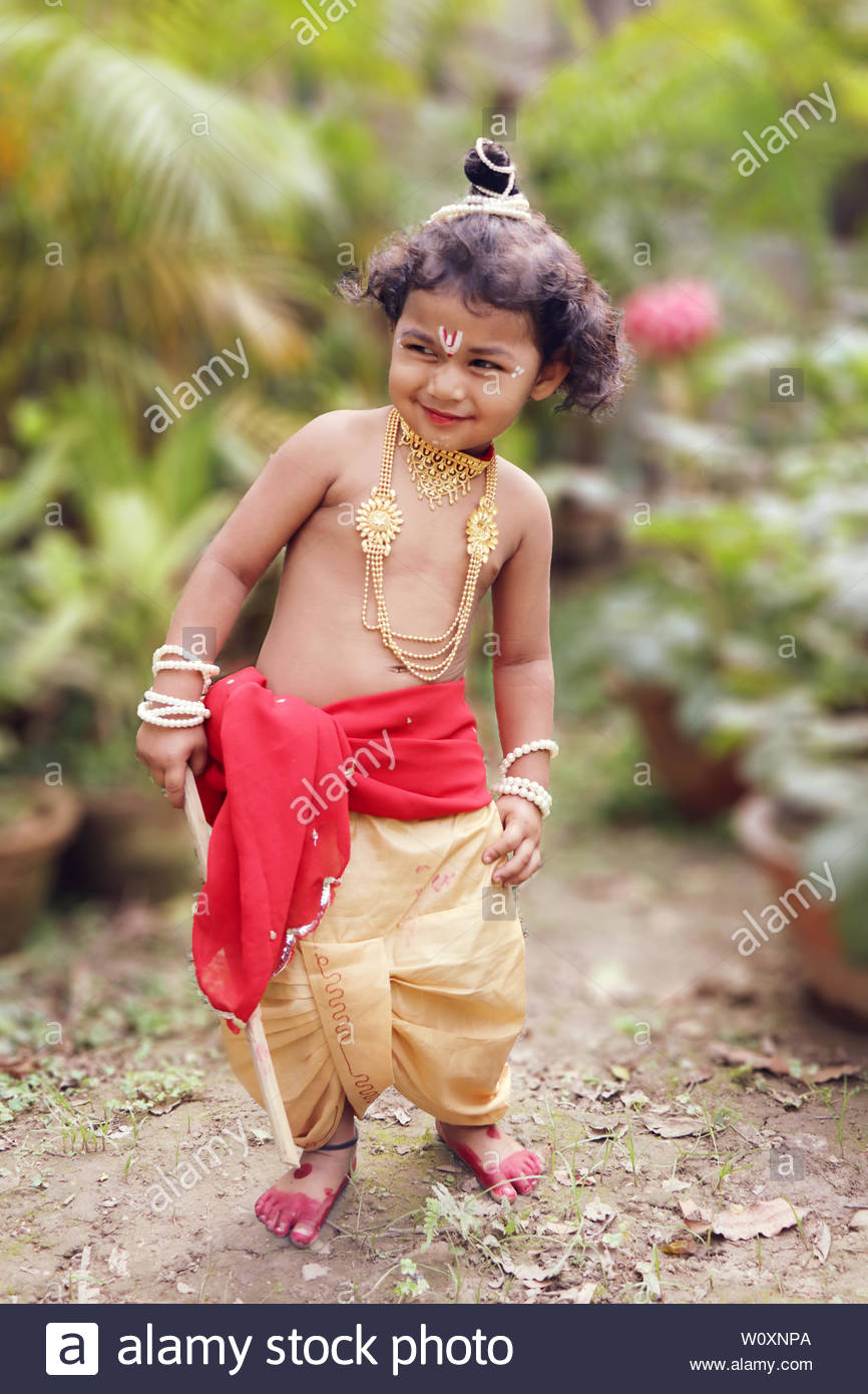 adorable baby boy dressed up as little krishna and playing with wooden flute in garden on the occasion of krishna janmastami W0XNPA