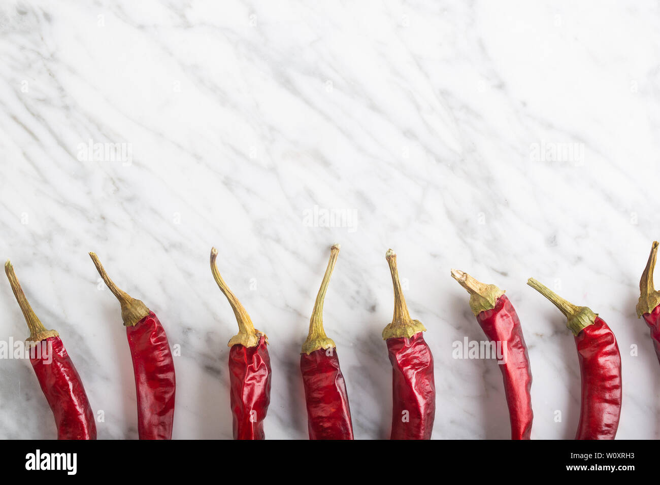Spicy Chili peppers on stone background  This condiment