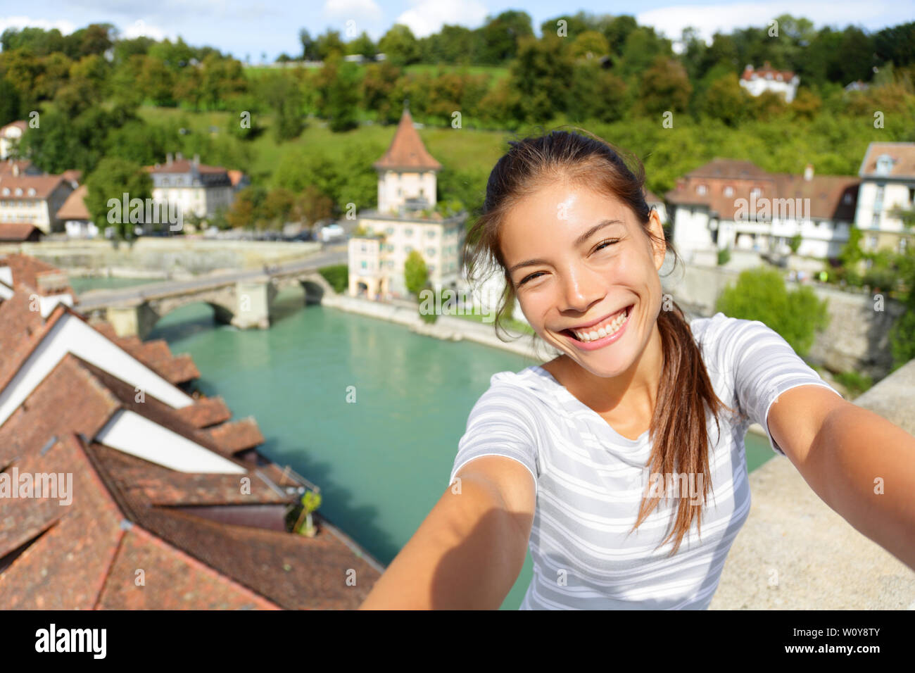 Travel selfie by woman in Bern Switzerland. Happy smiling multiracial Asian Caucasian girl taking self portrait photograph sitting on Nydeggbrucke by Aare river in the Swiss city of Bern. - Stock Image