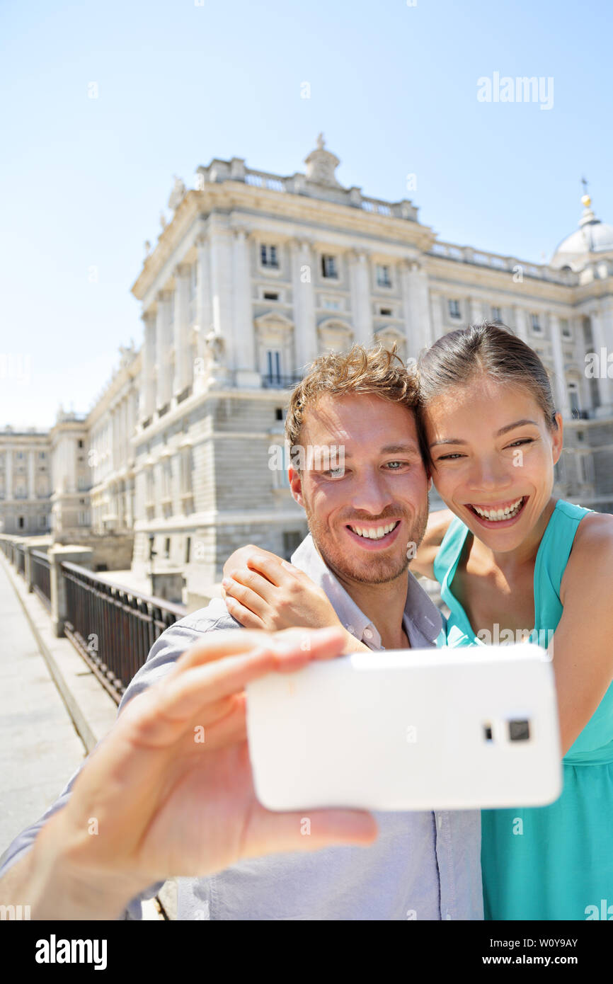 Couple taking selfie photo on smartphone in Madrid. Romantic man and woman in love using smart phone to take self-portrait photograph on travel in Madrid, Spain. - Stock Image