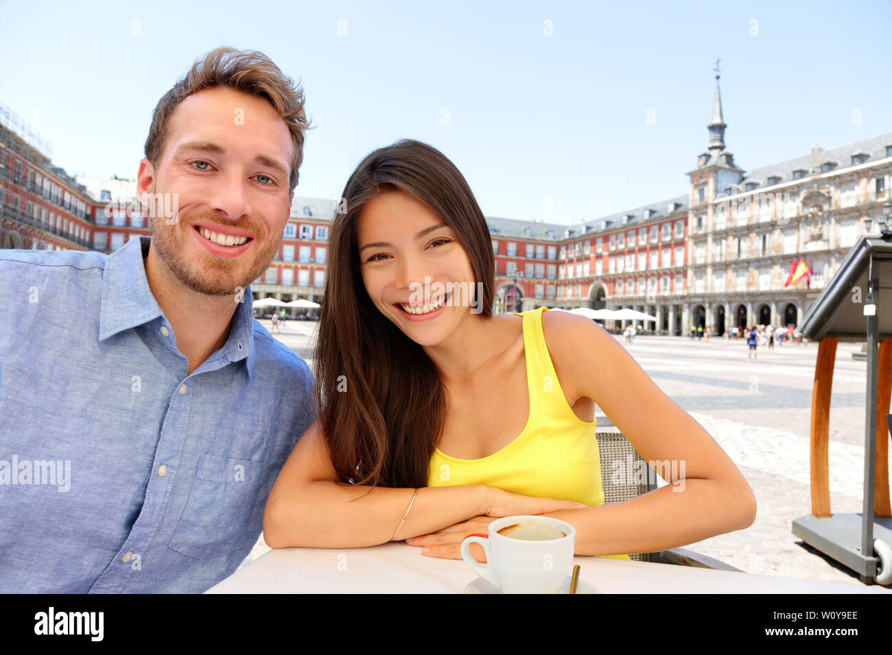 Madrid tourists taking selfie picture at cafe drinking coffee having fun on Plaza Mayor. Portrait of tourist couple sightseeing visiting tourism landmarks and attractions in Spain. Young woman and man Stock Photo