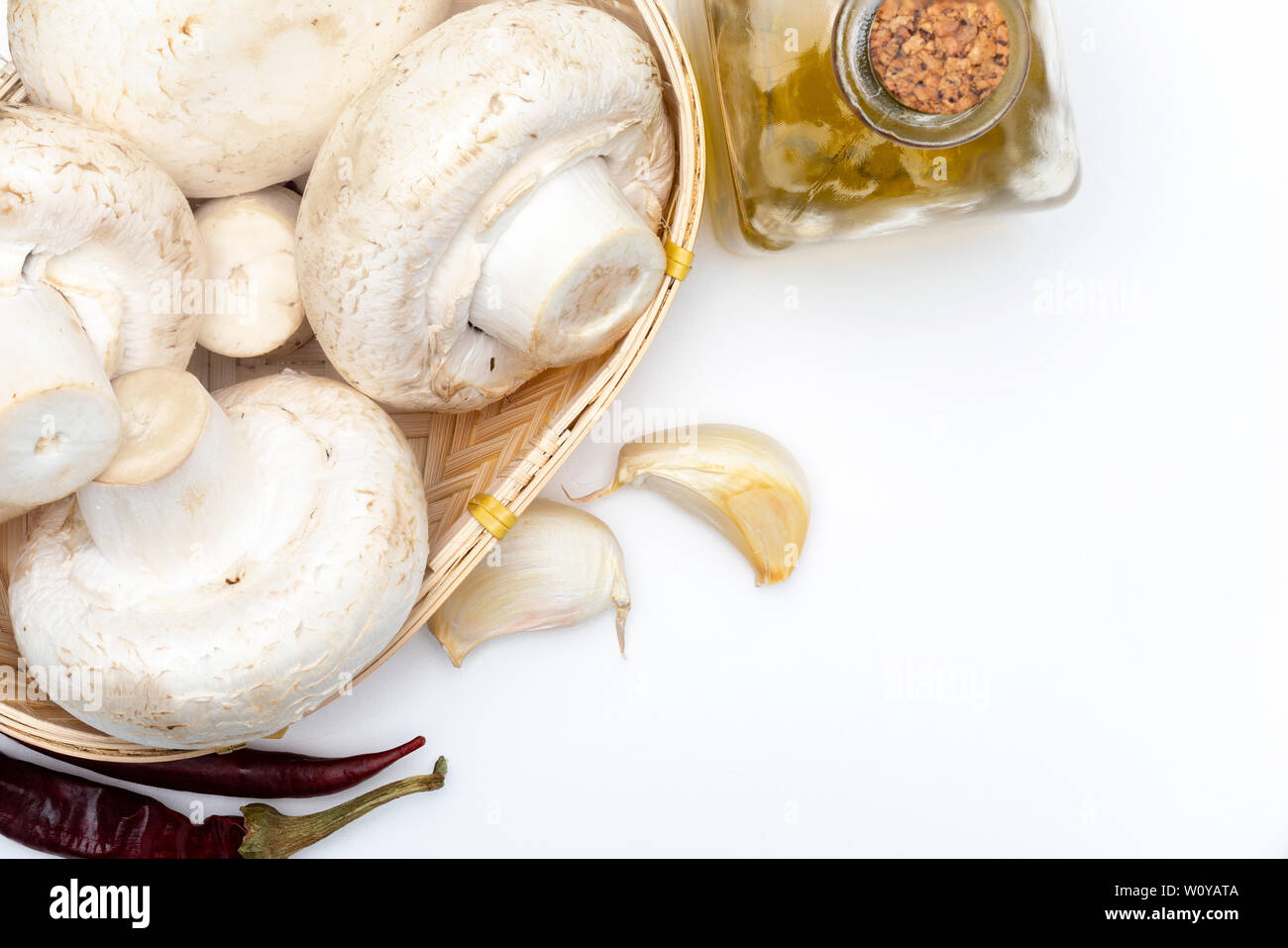 Basket of mushrooms (champignon, cut feet, Agaricus Bisporus) raw (uncooked). With several ingredients (olive oil, garlic and chilli pepper). White ba - Stock Image