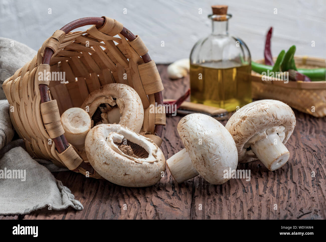 Basket of mushrooms (champignon, cut feet, Agaricus Bisporus) raw (uncooked). With several ingredients (olive oil, garlic and chilli pepper). Wood bac - Stock Image