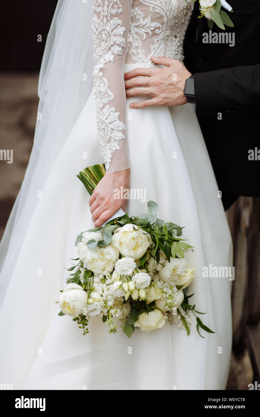The Bride In An Elegant Wedding Dress Holds A Beautiful Bouquet Of