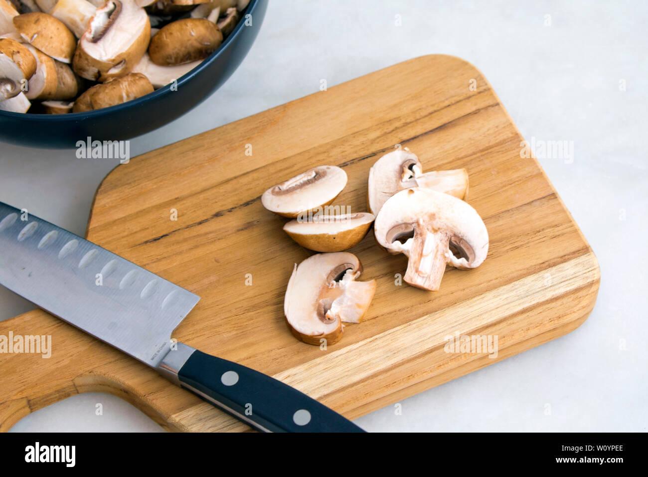 Slicing Cremini Mushrooms on a Wood Cutting Board - Stock Image