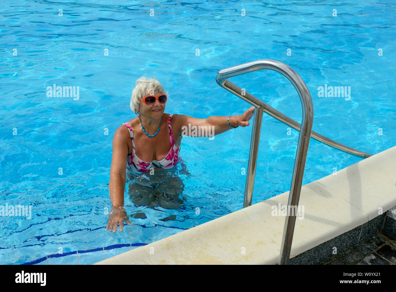 Elderly smiling blonde lady that holds her hand on handrails ...