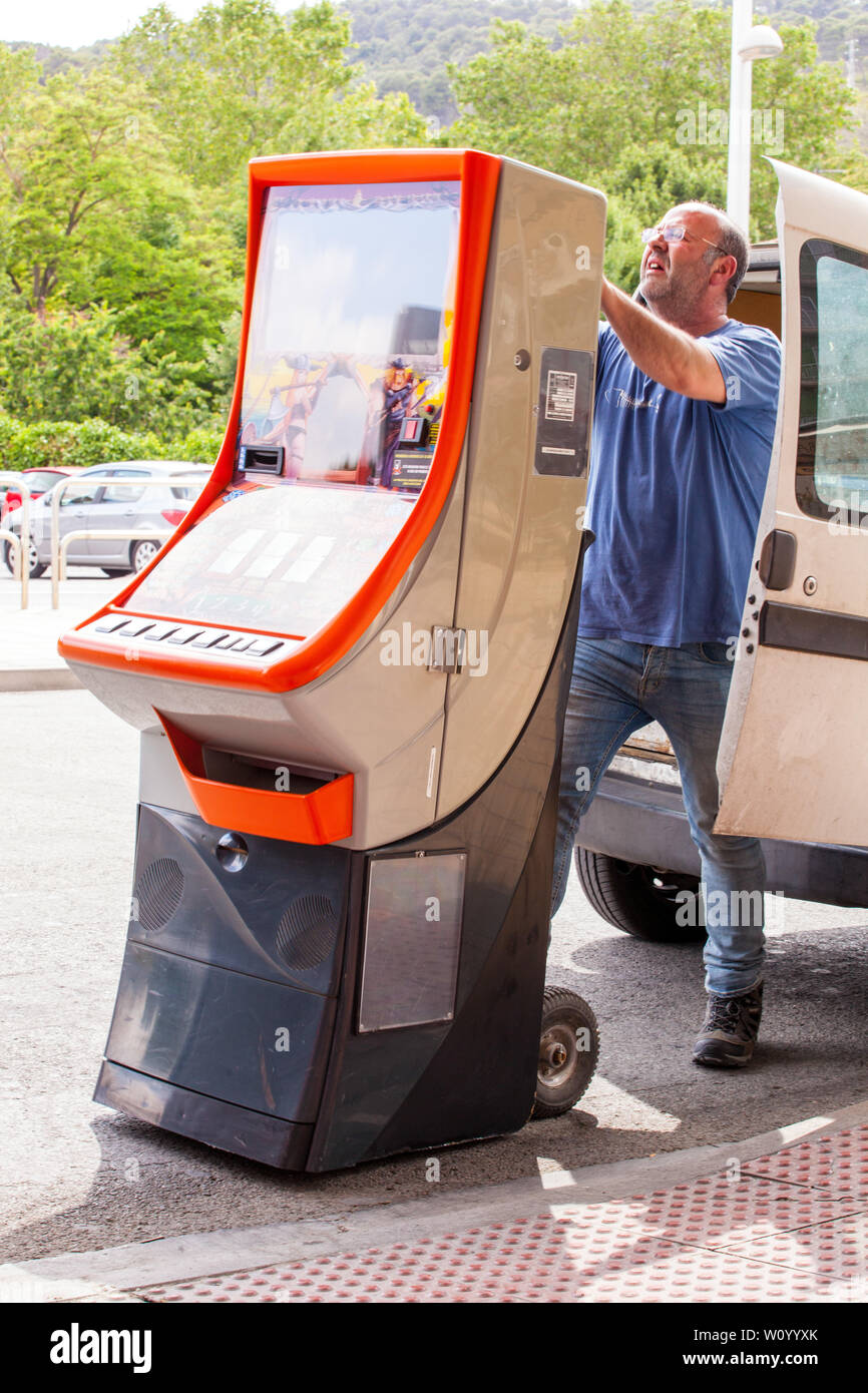 Man loading a betting shop fixed odds gaming machine into the back of a van - Stock Image
