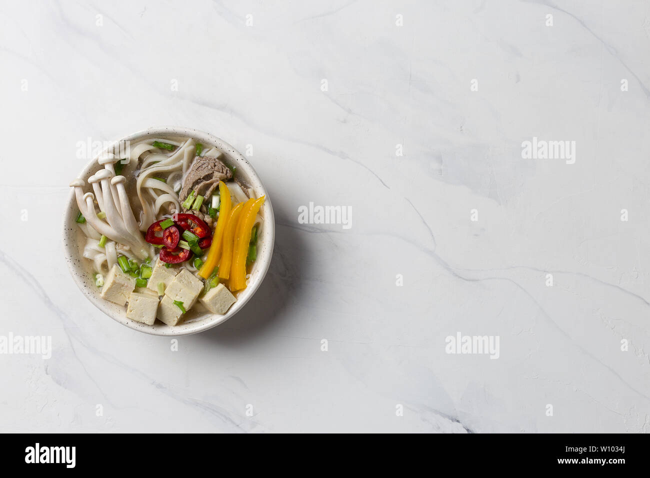 Heated noodle soup with beef, mushrooms and vegetables on white background. Copy space for text. - Stock Image