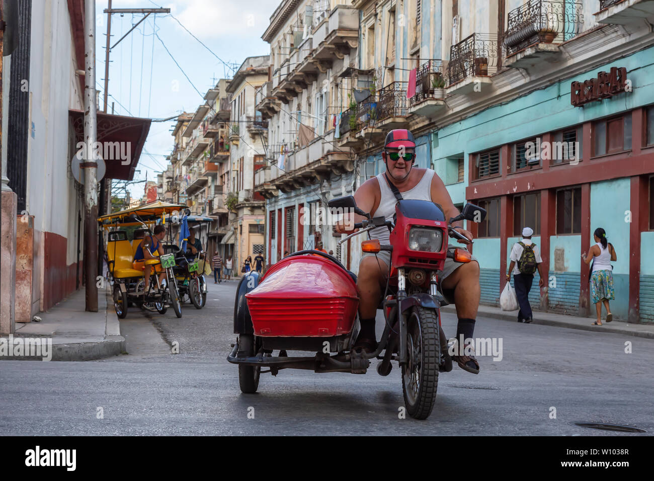 Havana, Cuba - May 13, 2019: Cuban man riding a motorcycle in the streets of Old Havana City during a vibrant and bright sunny day. Stock Photo