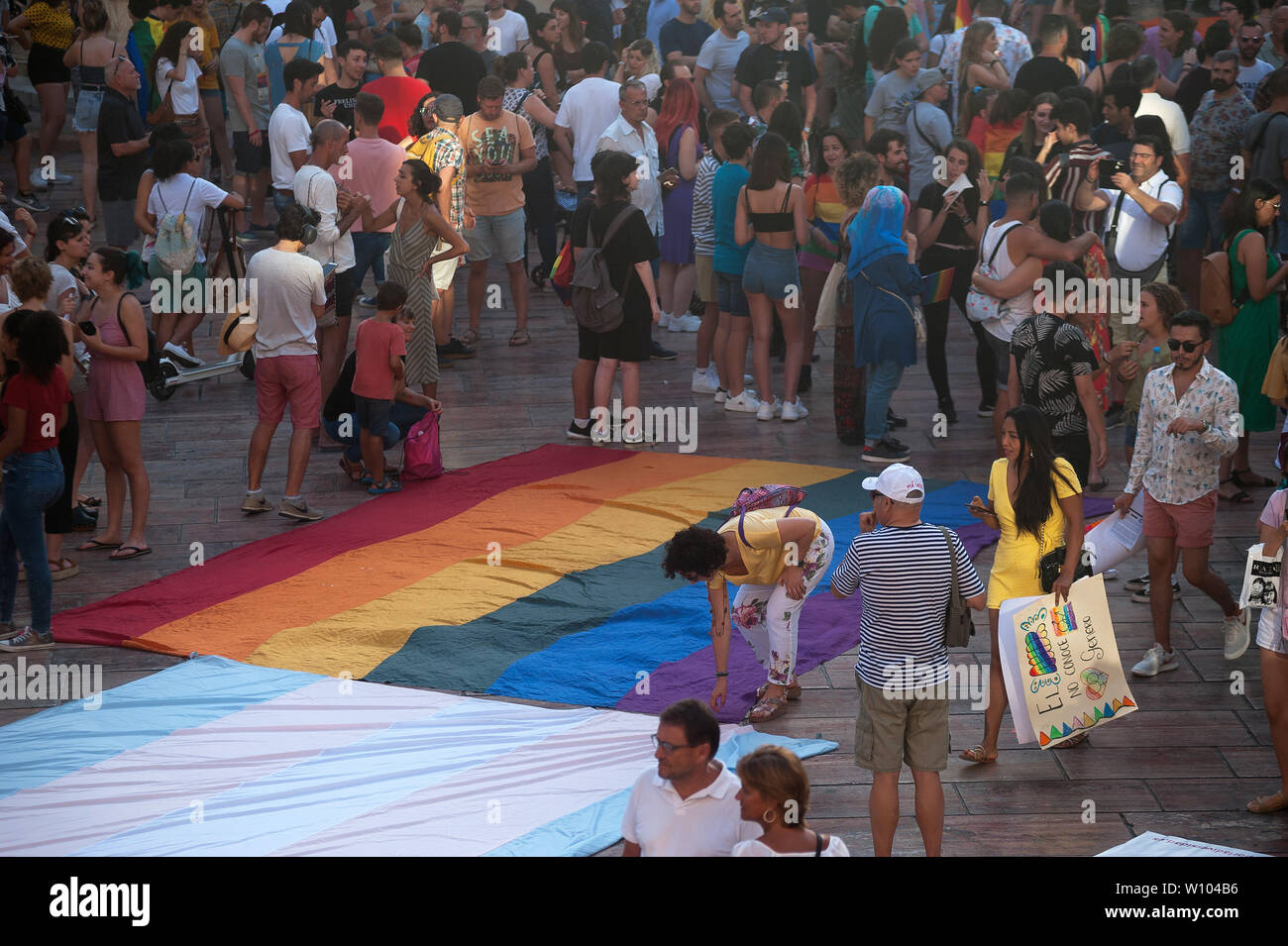 People gather around a large pride flag during a demonstration to celebrate the International Pride LGTBI Day 2019, organized by Andalusia Rainbow Federation.Thousands of people around the world take part on the Pride LGTBI, marked the anniversary of 50 years of Stonewall riot which commemorated the fight of gays, lesbians, transgender, bisexuals and intersexual during the first demonstrations in US in favour of their rights. Stock Photo