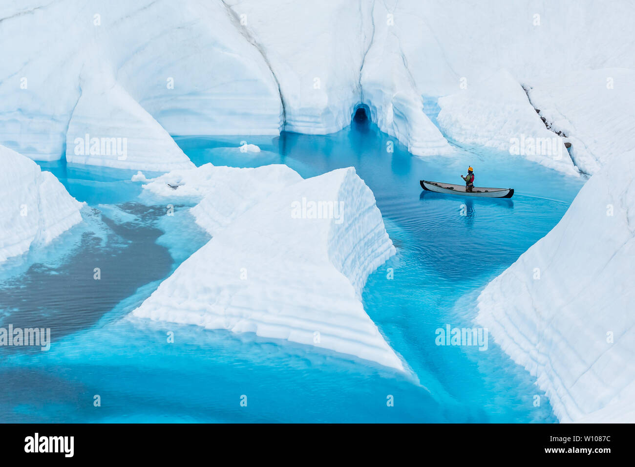 On the Matanuska Glacier in Alaska, an ice climbing guide floats an inflatable canoe on a deep blue lake on the glacier. The narrow flooded canyons le Stock Photo