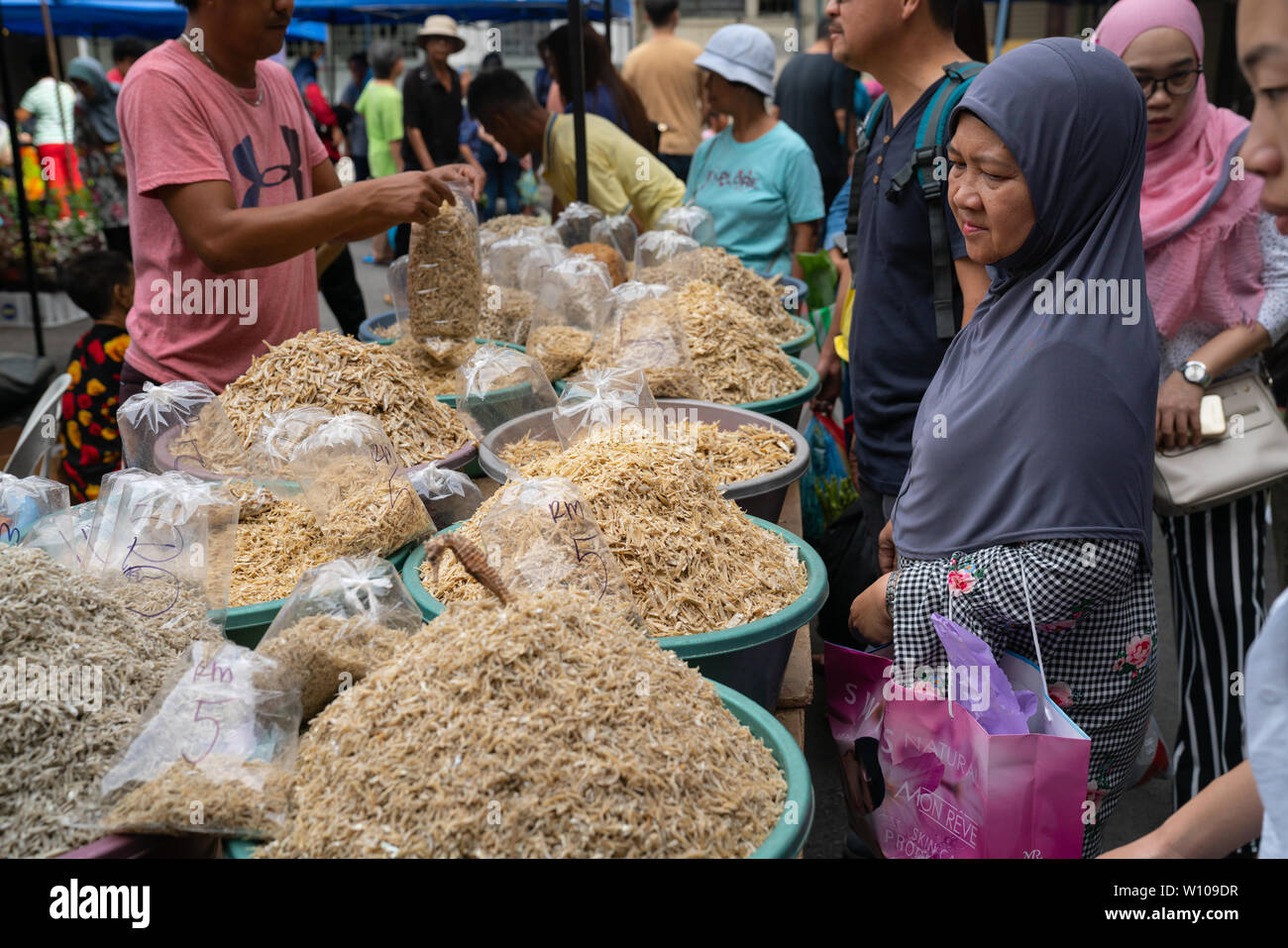 KOTA KINABULU, BORNEO - JUNE 2  Dried fish seller in Kota Kinabalu Gaya Street Sunday market packs product for buyer and hands it over. - Stock Image