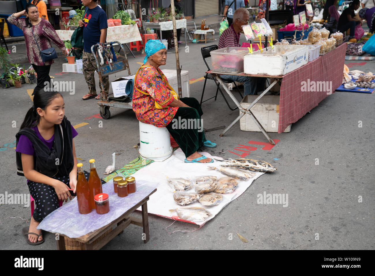KOTA KINABULU, BORNEO - JUNE 2  PACKS PRODUCT FOR CUSTOMER.  Kota Kinabalu Sunday market seller at their stall sitting waiting for buyers. - Stock Image