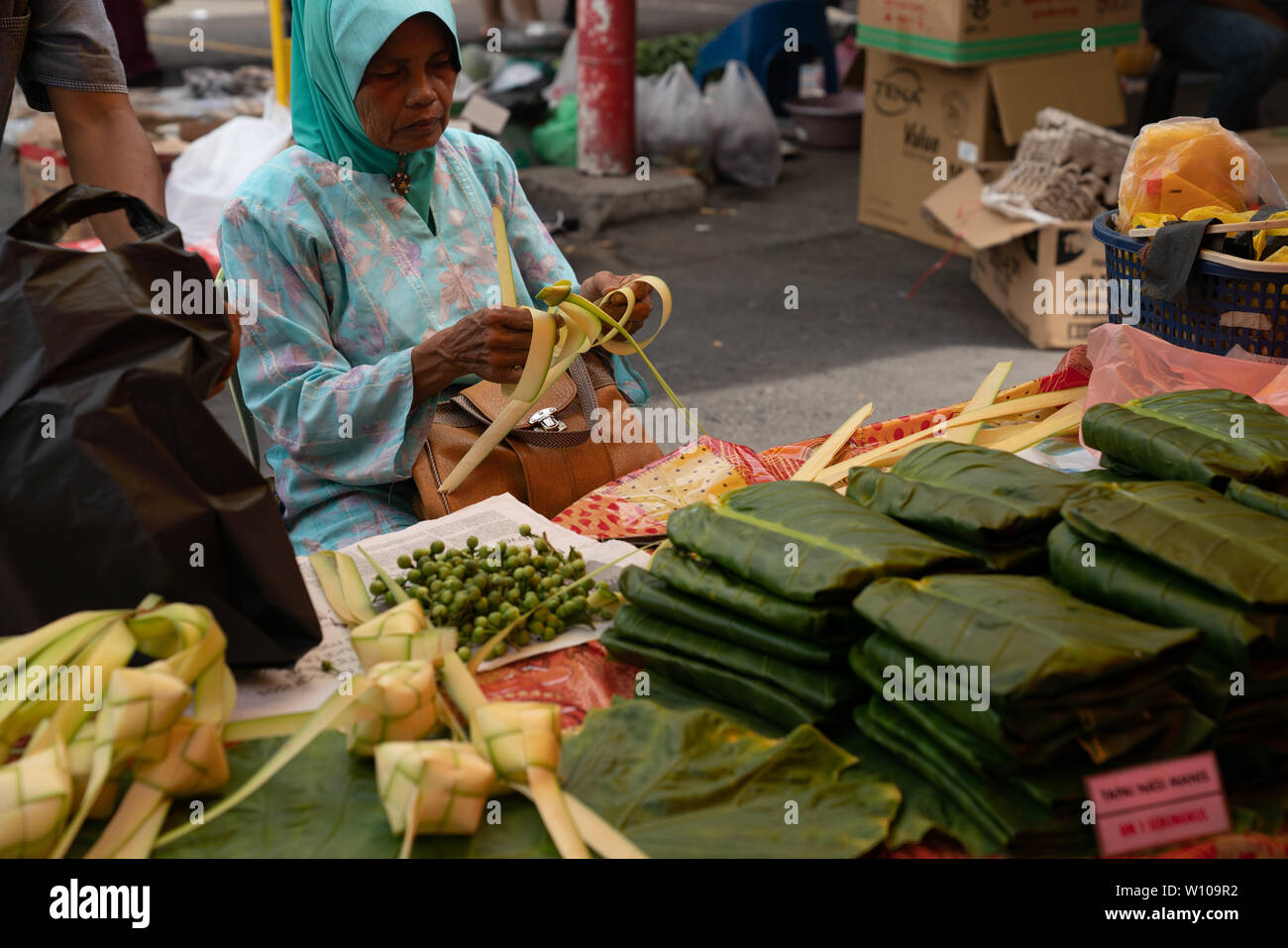 KOTA KINABULU, BORNEO - JUNE 2  PACKS PRODUCT FOR CUSTOMER.  Kota Kinabalu Sunday Gaya Street market seller  in Muslim attire making banana leaf wrapp - Stock Image