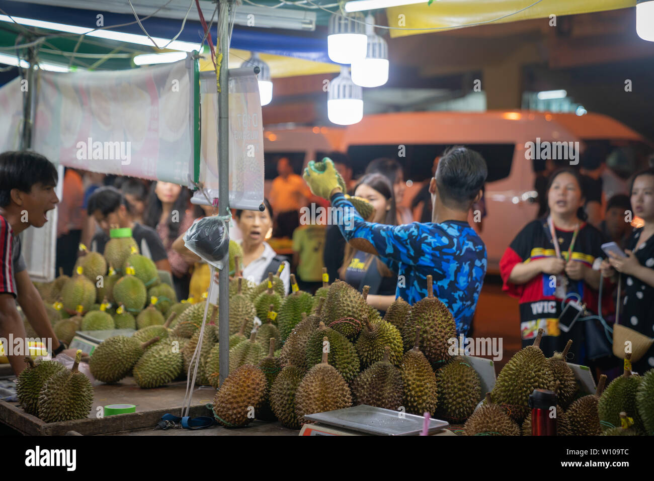 KOTA KINABULU, BORNEO - JUNE 1 2019; Night street market for locals  selling delicacy but smelly durian fruit stacked on bench vendor and passers-by. - Stock Image