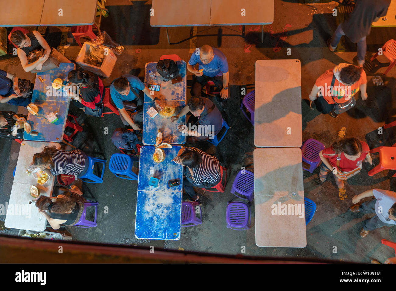 KOTA KINABULU, BORNEO - JUNE 1 2019; Night street market for locals eating delicacy but smelly durian fruit at tables in street - Stock Image
