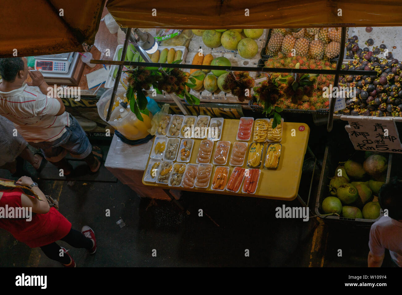 KOTA KINABULU, BORNEO - JUNE 1 2019; Night street market for locals with produce laid out on table wraaped in plastic - Stock Image