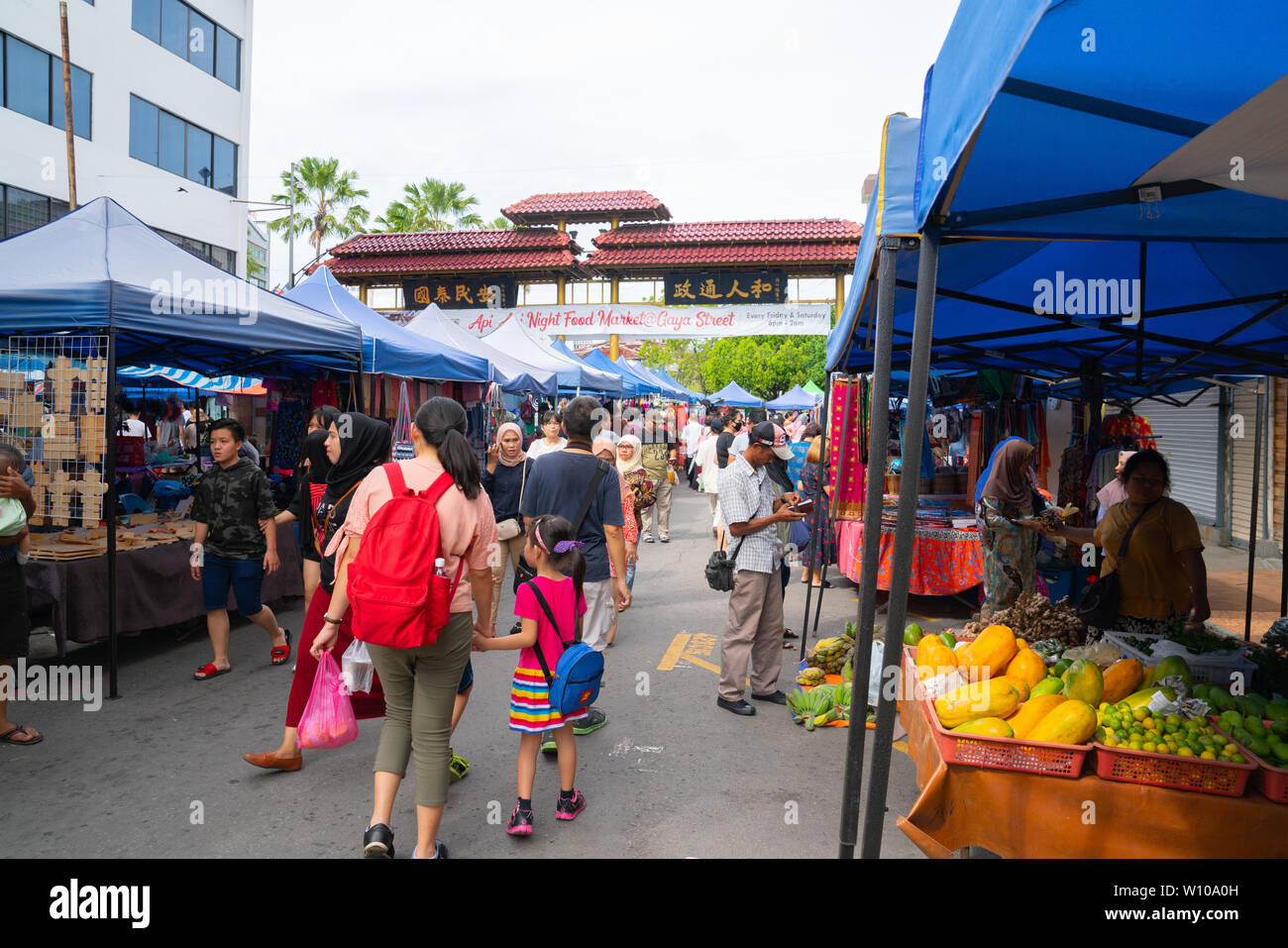 KOTA KINABULU, BORNEO - JUNE 2  PACKS PRODUCT FOR CUSTOMER.  Kota Kinabalu Gaya Street Sunday market  people throng between the stalls and vendors. - Stock Image