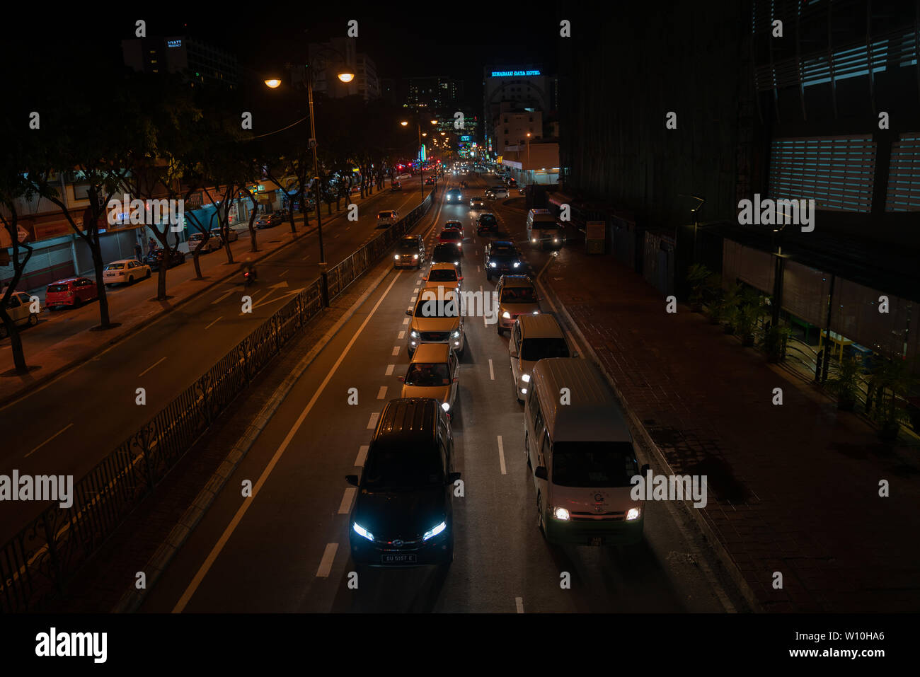 KOTA KINABALU BORNEO - JUNE 1 2019; Street scene with neon and vehicle lights and light trails and patterns from moving cars high point of view. - Stock Image