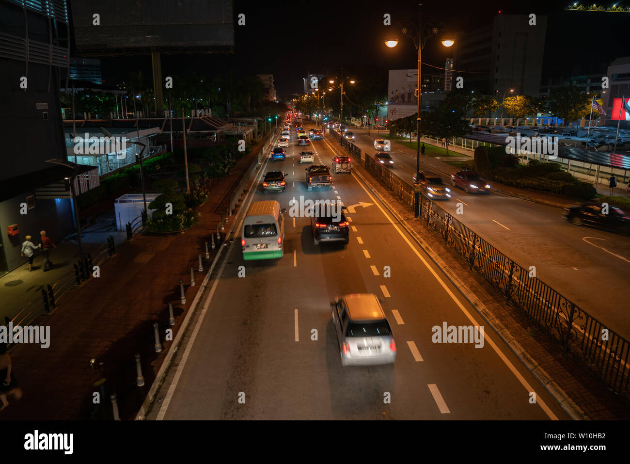 KOTA KINABALU BORNEO - JUNE 1 2019; Street scene with neon and moving vehicles blurred in motion on long street  high point of view. - Stock Image