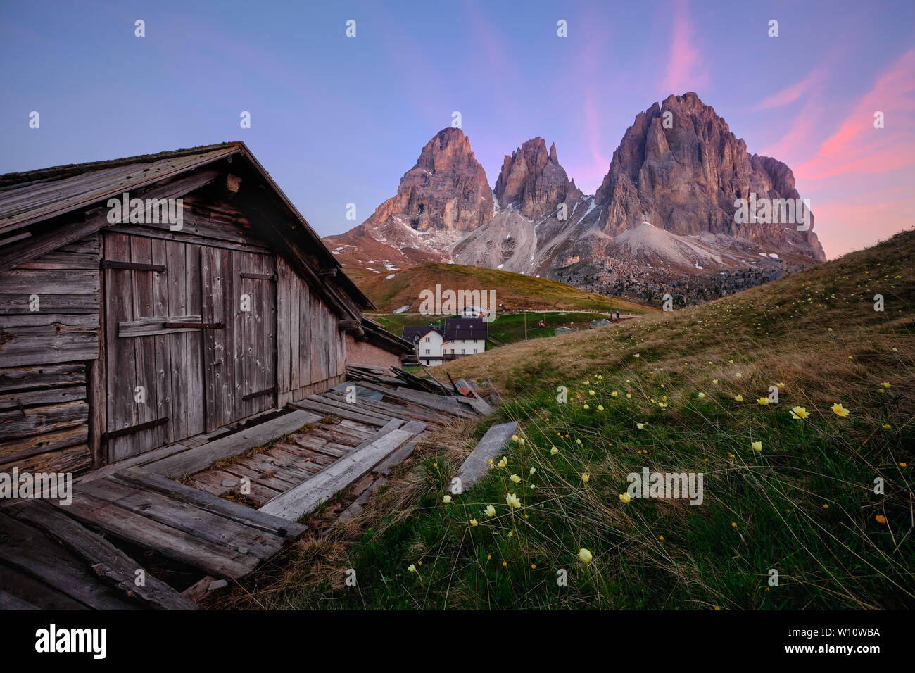 Old cabin in Dolomiti (Italy) with views to Sassolungo mountain at sunrise - Stock Image
