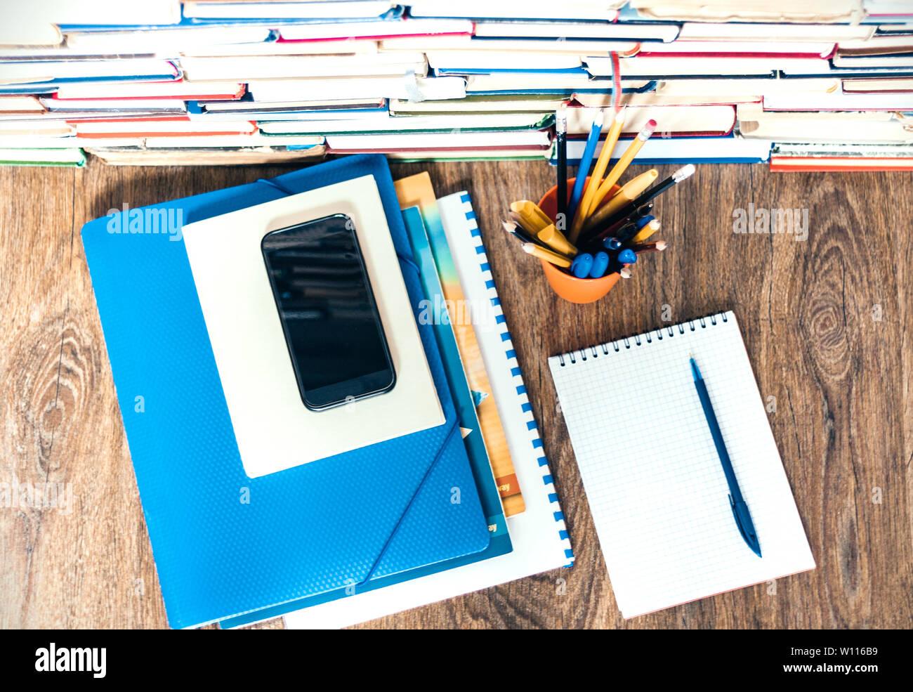 Stack of books, hardback books, smartphone, plastic folder
