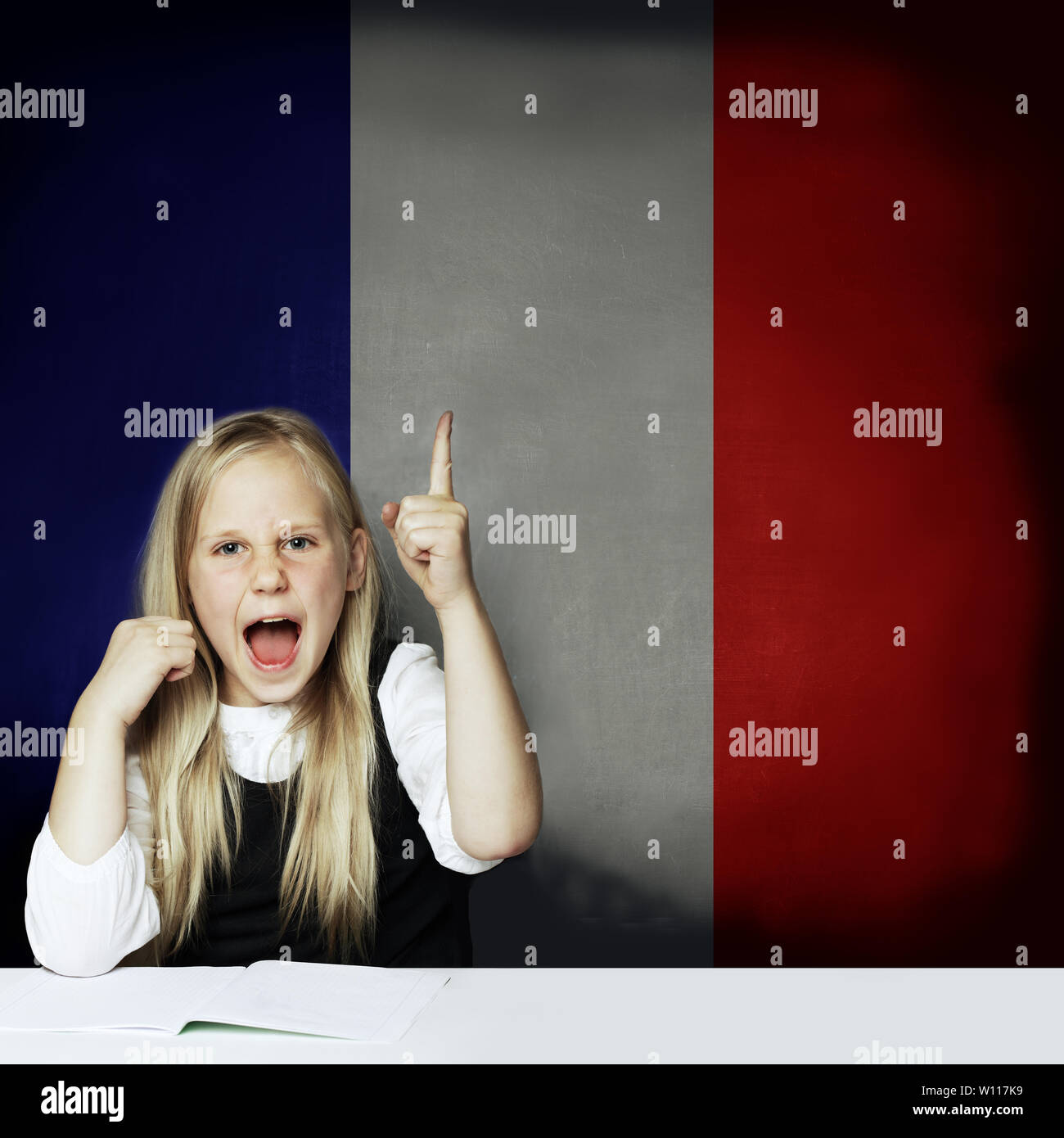 Learn french language concept. Happy child girl student pointing up and having fun against the France flag background. - Stock Image