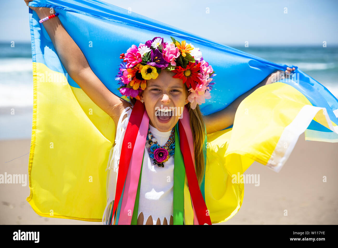 Happy Ukrainian girl holds blue and yellow flag of Ukraine against blue sky and sea background. Ukrainian flag is a symbol of Independence Stock Photo