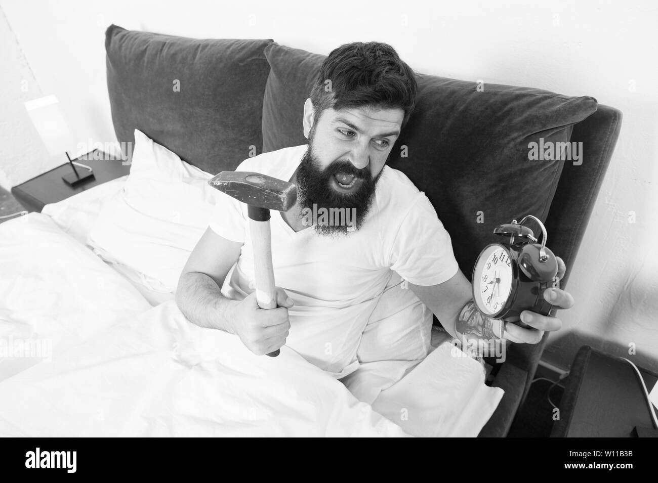 Overslept again. Tips for waking up early. Tips for becoming an early riser. Man bearded hipster sleepy face in bed with alarm clock. Problem with early morning awakening. Get up with alarm clock. - Stock Image