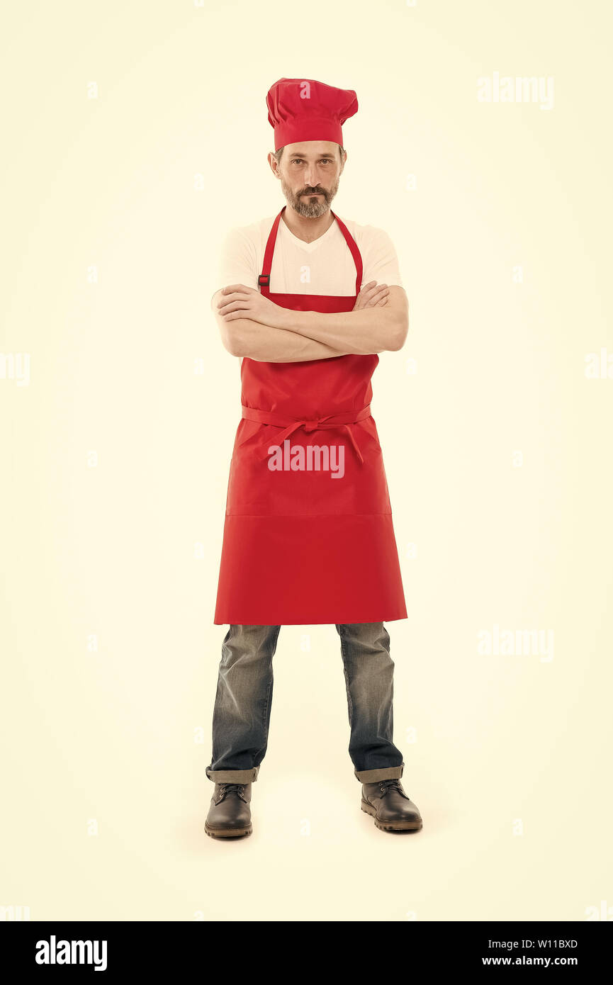 Known for his cooking. Bearded mature man in chef hat and apron. Senior cook with beard and moustache wearing bib apron. Mature chief cook in red cooking apron. Home cooking. - Stock Image