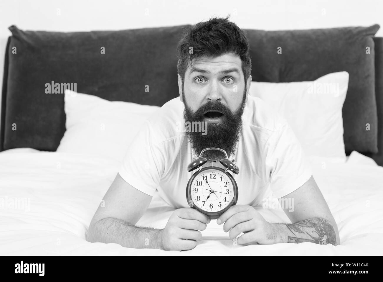 Tips for becoming an early riser. Problem with early morning awakening. Get up with alarm clock. Overslept again. Tips for waking up early. Man bearded hipster sleepy face in bed with alarm clock. - Stock Image