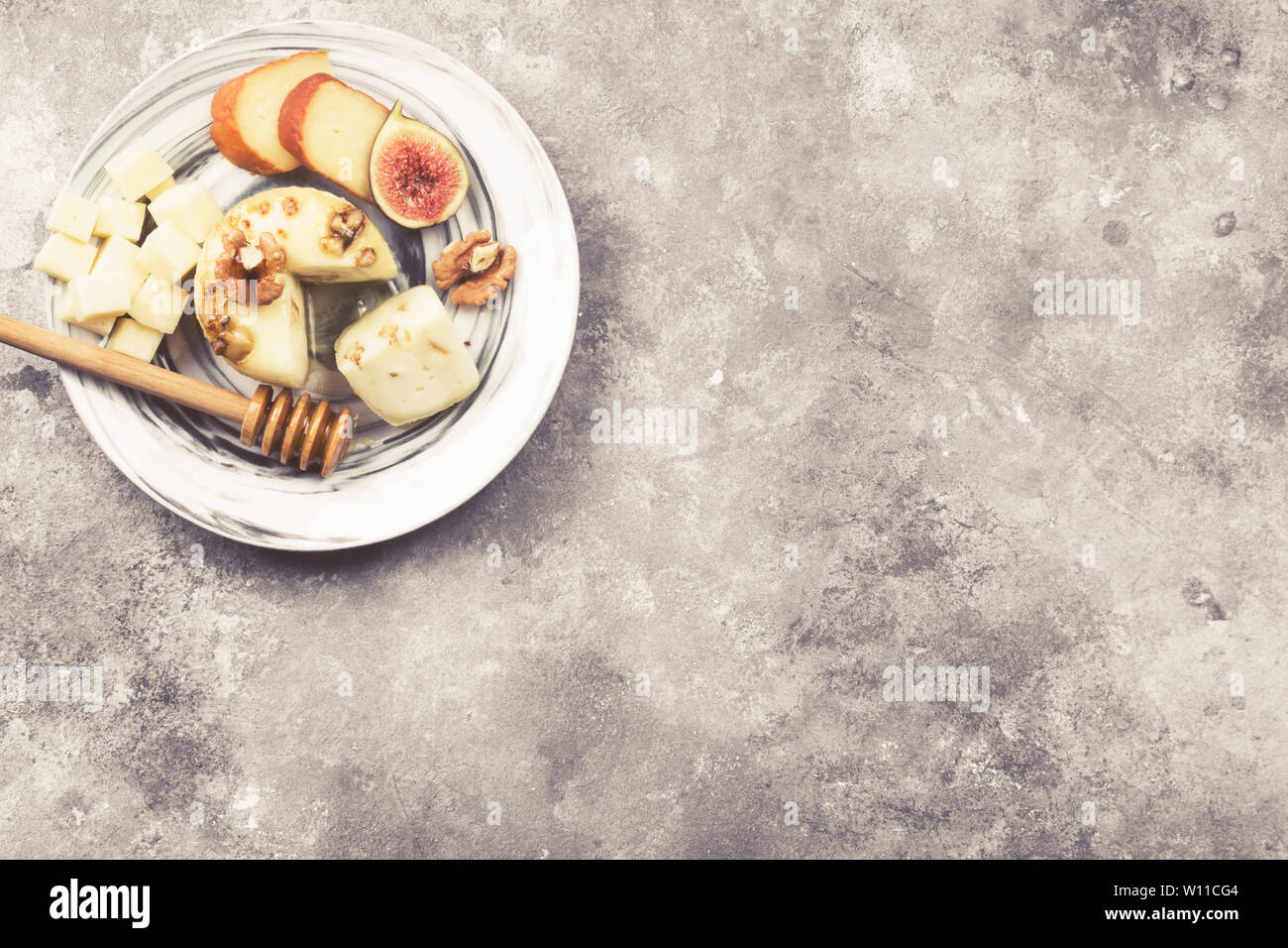 Snacks with wine - various types of cheeses, figs, nuts, honey on a gray background. Top view, copy space. Food background. Toned Stock Photo