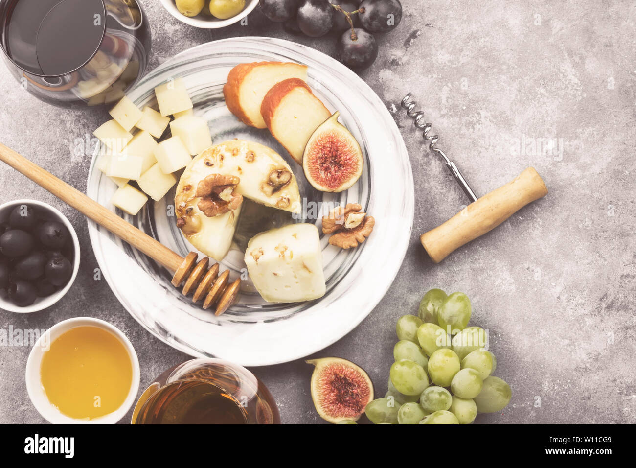 Snacks with wine - various types of cheeses, figs, nuts, honey, grapes on a gray background. Top view, copy space. Food background. Toned Stock Photo