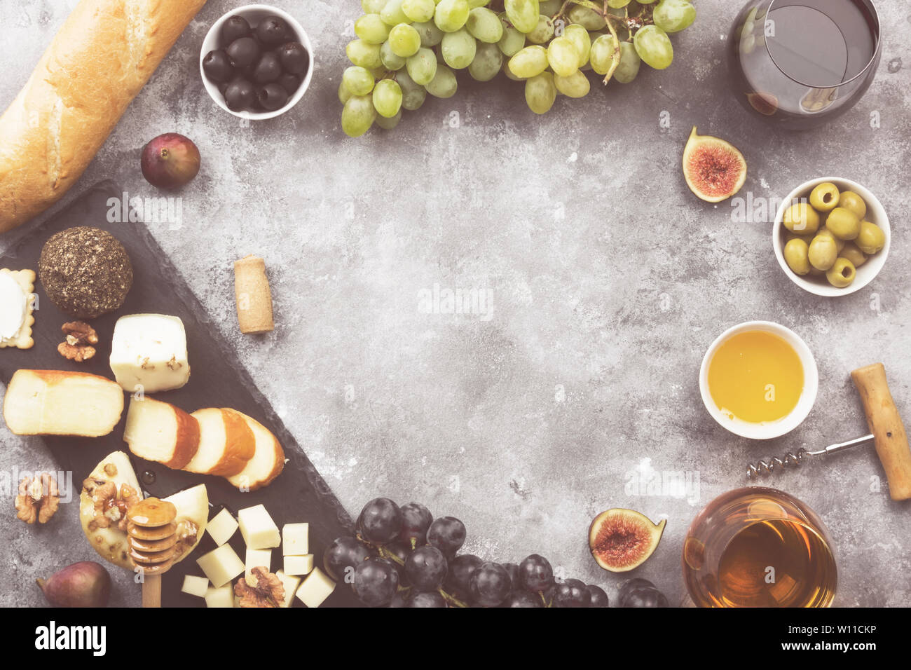 Snacks with wine - various types of cheeses, figs, nuts, honey, grapes, bread on a gray background. Top view, copy space. Food background. Toned Stock Photo