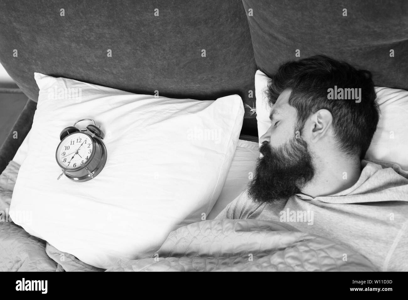Man bearded hipster sleepy face in bed with alarm clock. Problem with early morning awakening. Get up with alarm clock. Overslept again. Tips for waking up early. Tips for becoming an early riser. - Stock Image