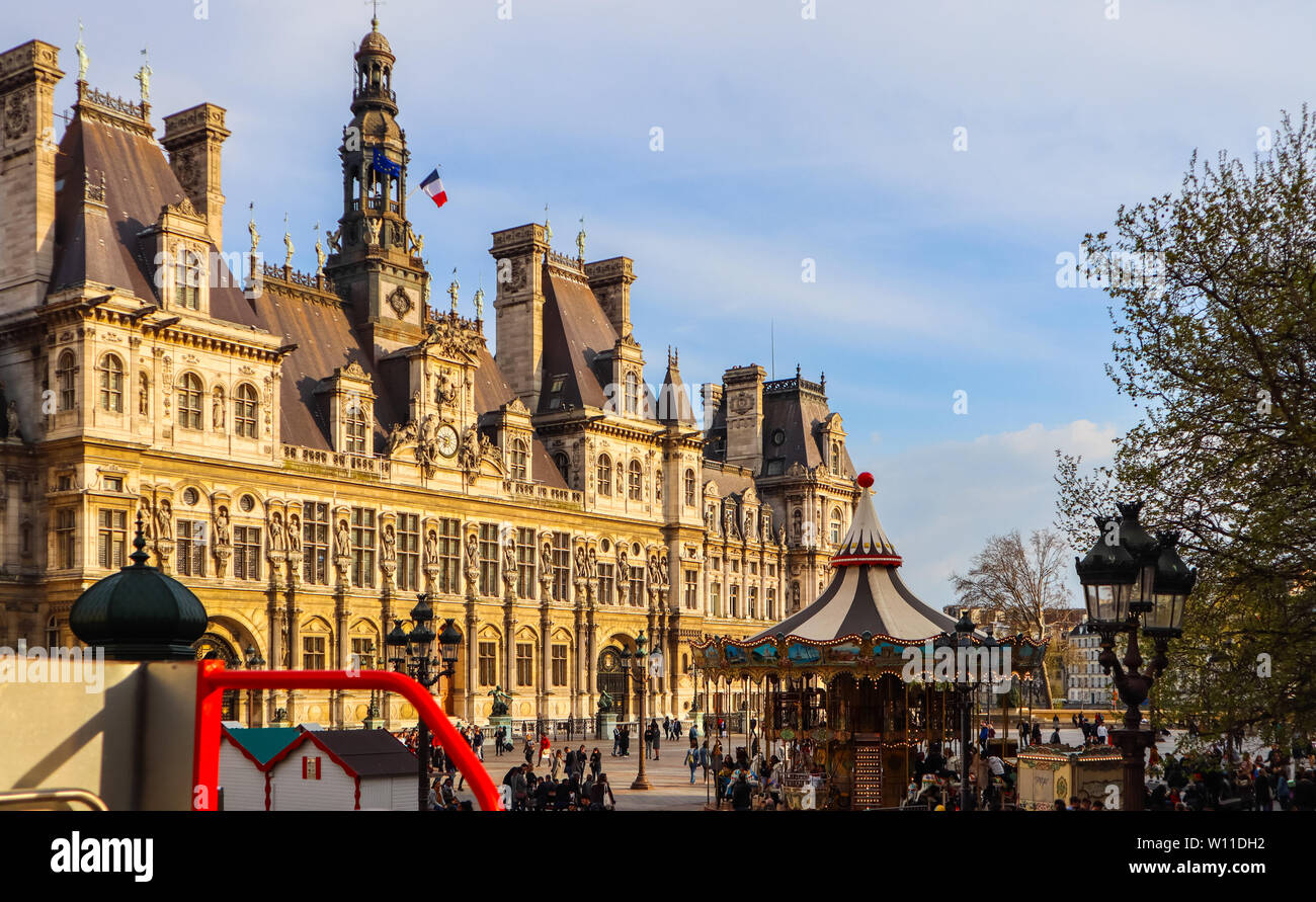 View from the touristic bus on the square in front of Hotel de Ville, the Municipality of Paris, full of resting people at sunset in spring. Paris Fra - Stock Image