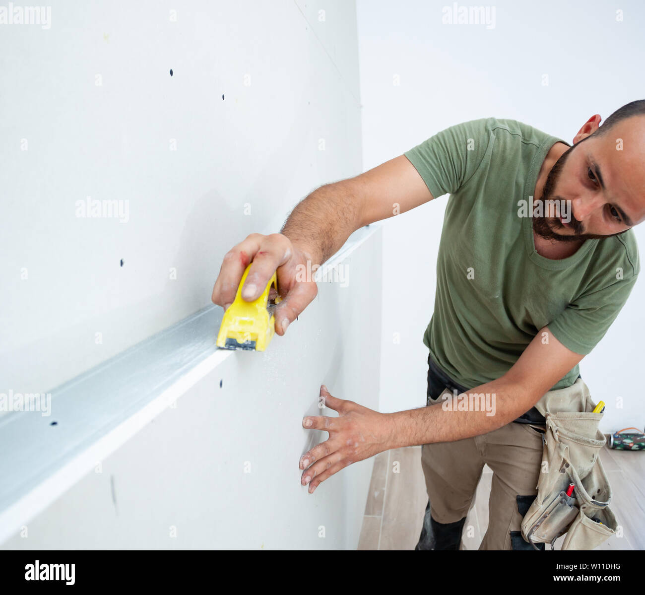 Worker building plasterboard wall  Working with cutting tools