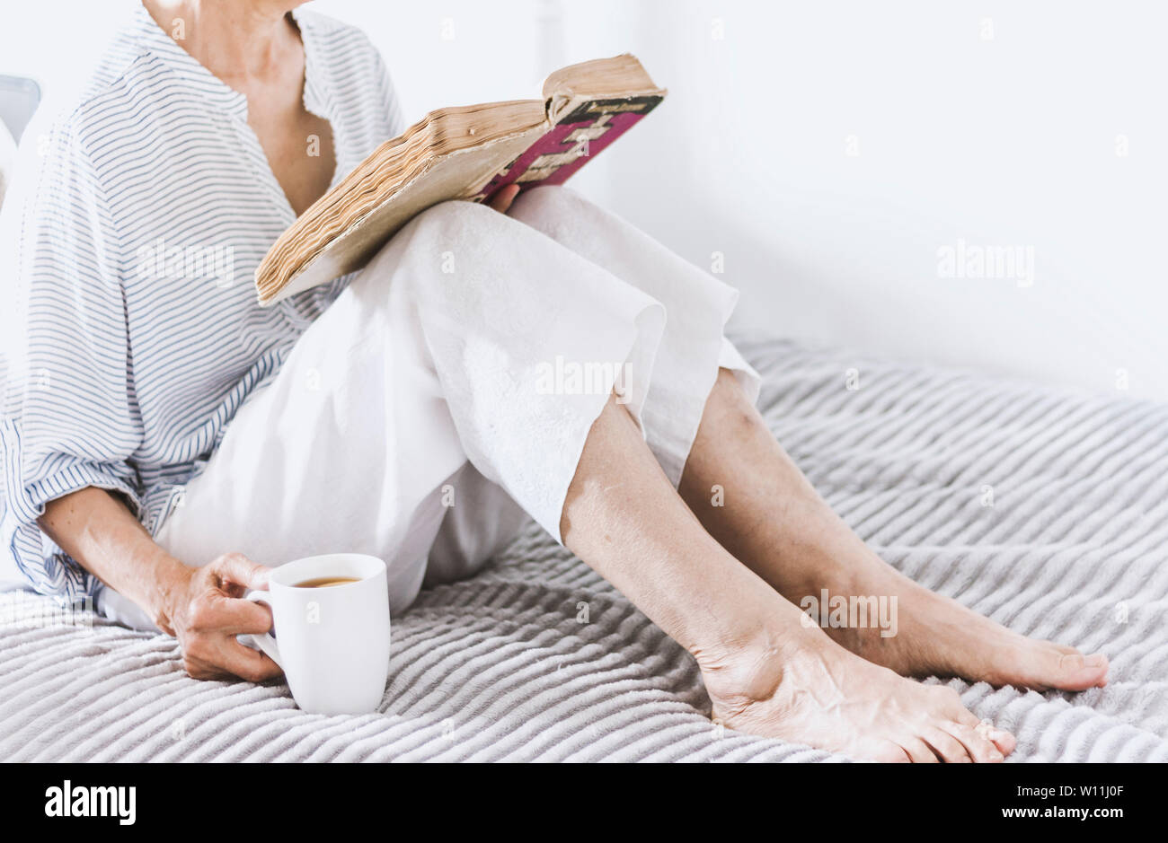 Old woman on the bed reading old book with cup of lemon tea Stock