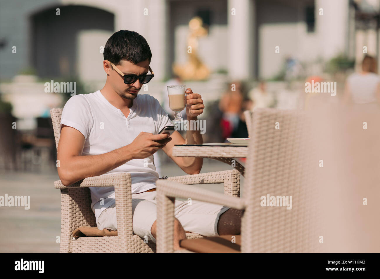 portrait of man in sunglasses sitting in a cafe and drinking coffee on a sunny summer day. Stock Photo