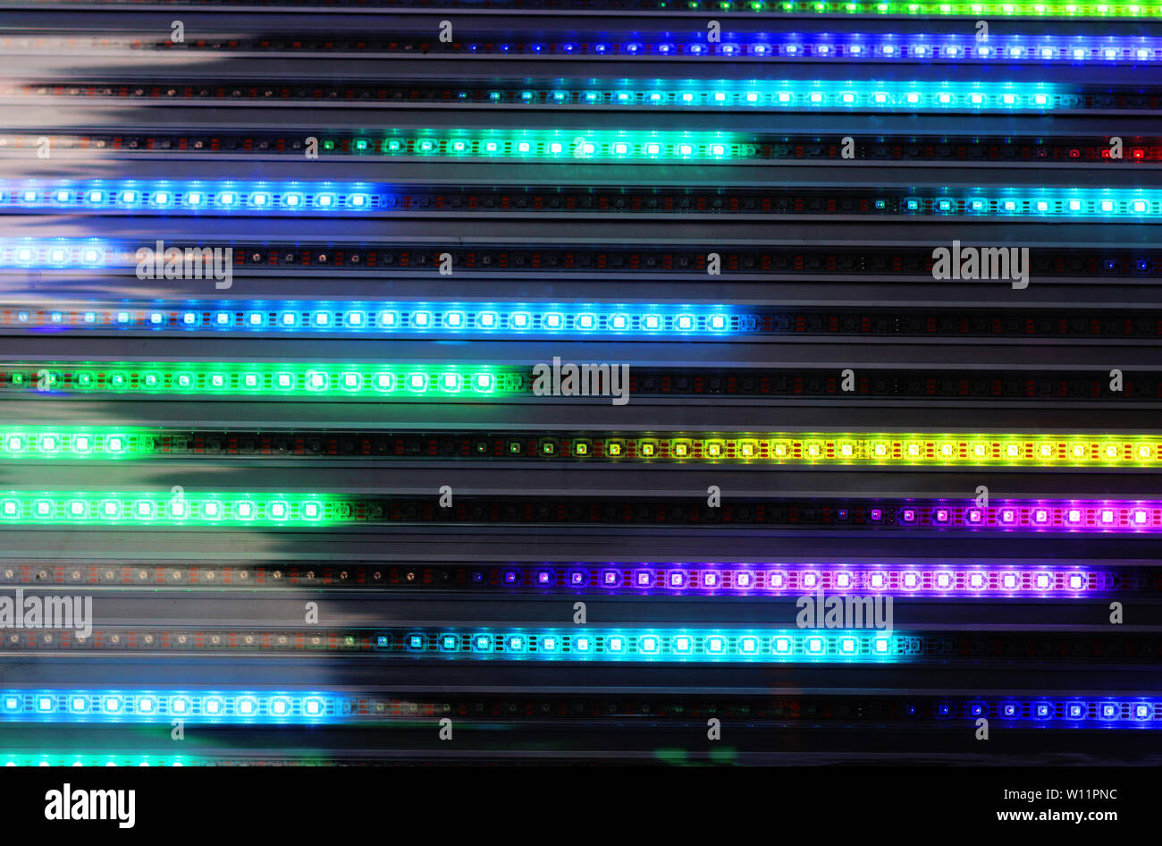 multi colored background with horizonal light lines shining green, blue and yellow - Stock Image