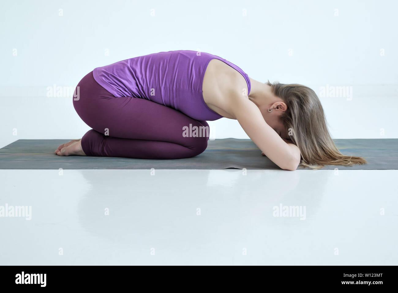 Caucasian woman practices yoga asana balasana or child pose - Stock Image