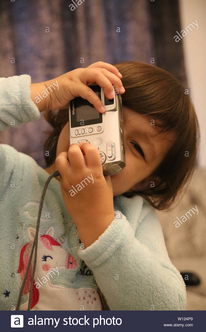 Lifestyle / Portraits - A happy two-year old girl holding a digital camera pretends to take a photograph. - Stock Image