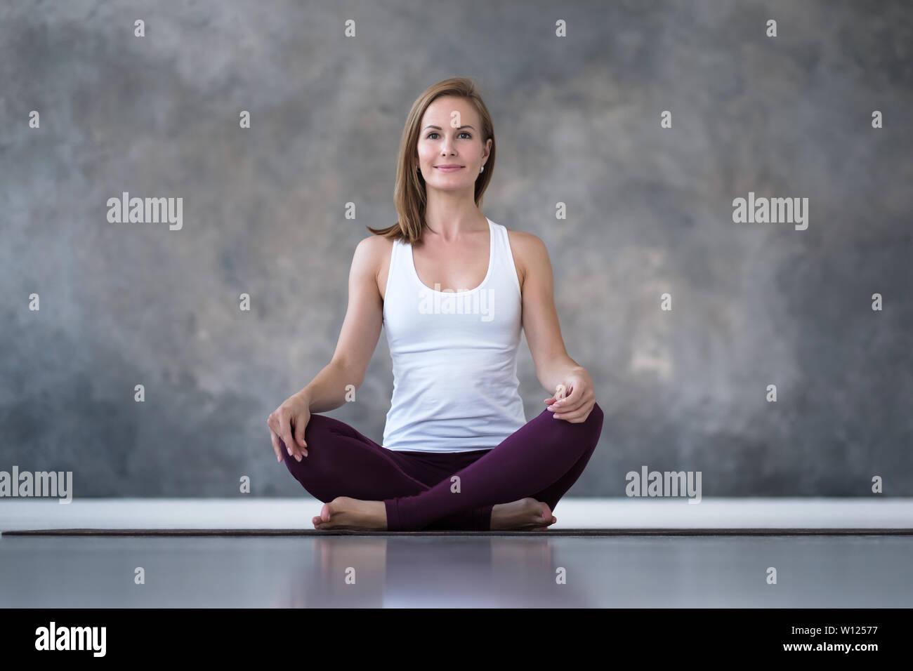 Caucasian woman practicing yoga, doing sukhasana or easy seat pose - Stock Image