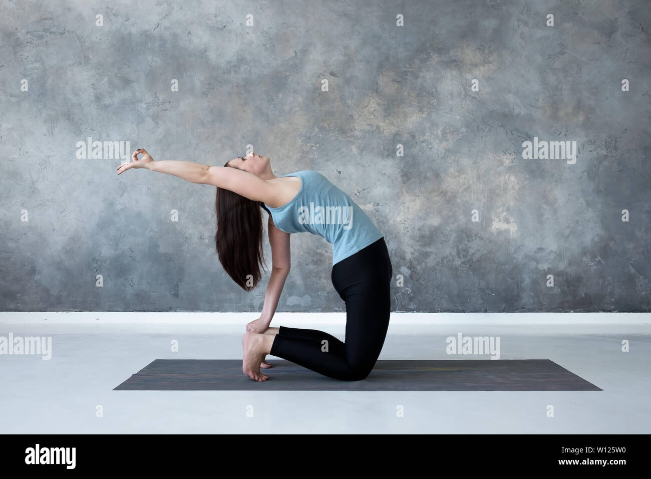 Woman practicing yoga, doing Ushtrasana, Camel Pose, at studio full length. - Stock Image
