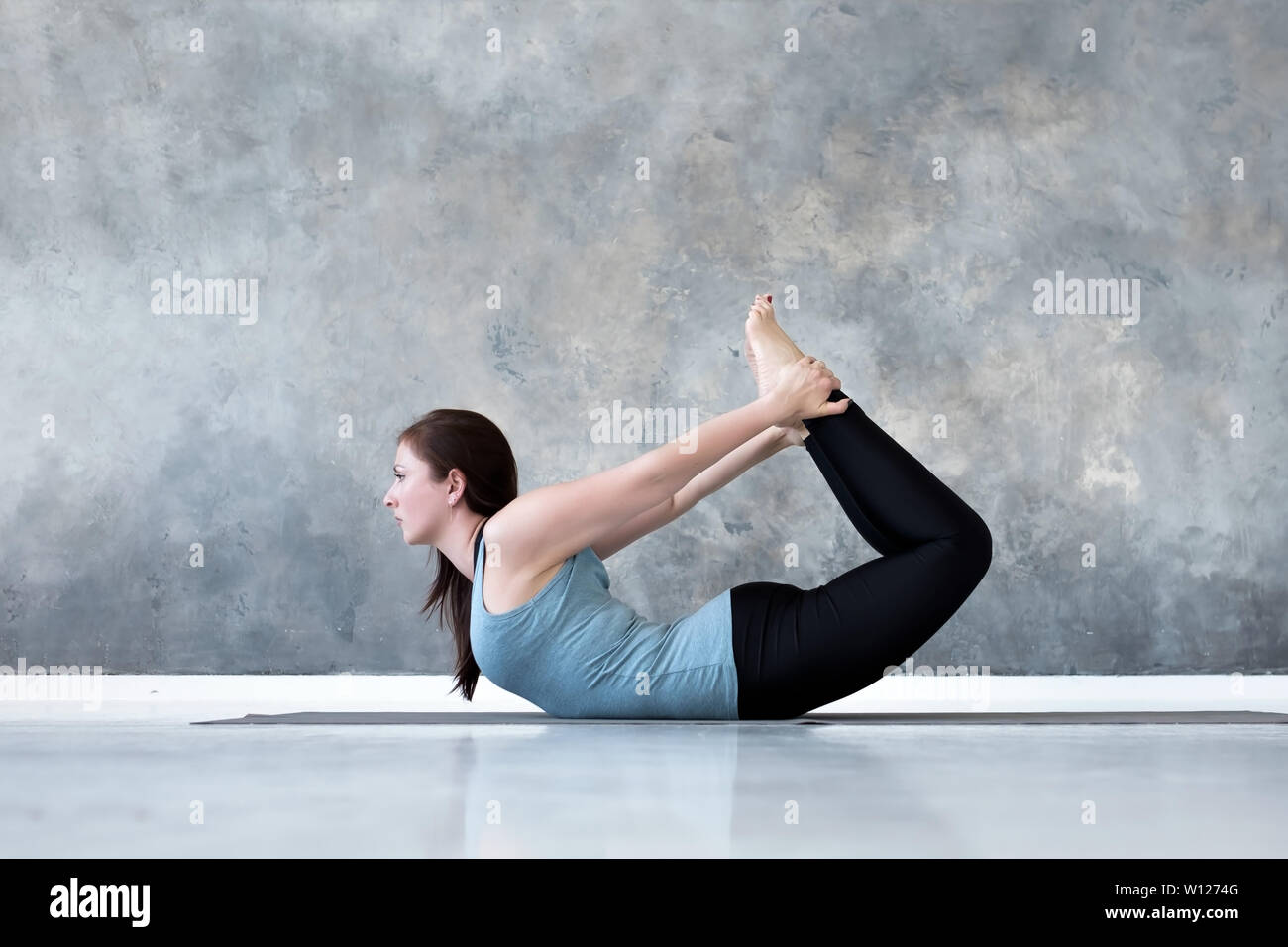 Young woman practicing yoga Bow pose, Dhanurasana Stock Photo