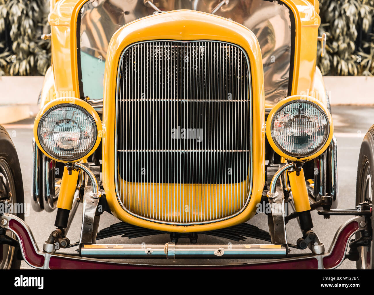 yellow color vintage car head view from front - Stock Image