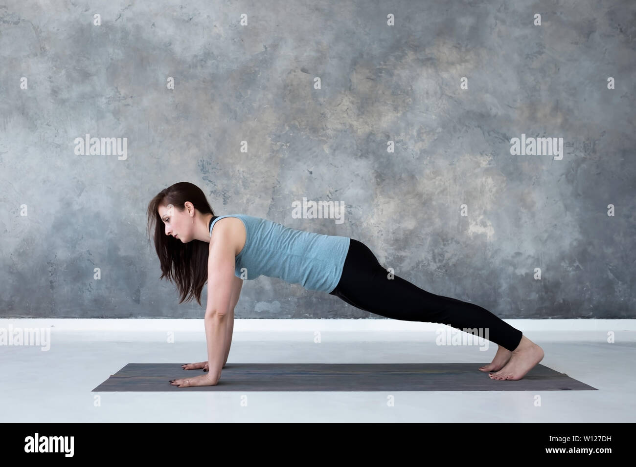 Young woman practicing yoga, doing Push ups or press ups exercise, Plank pose. - Stock Image