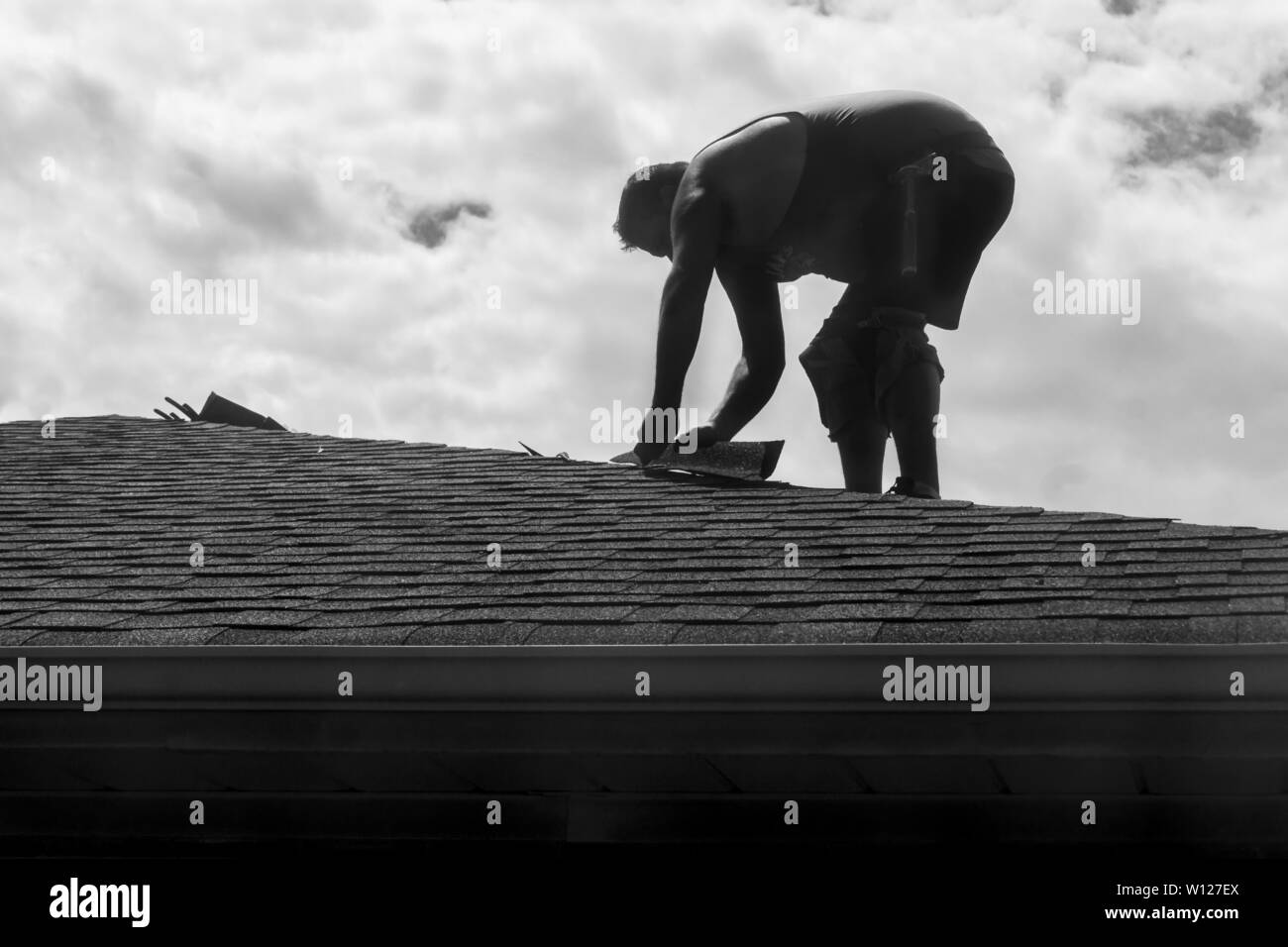Toronto, Canada - One man replacing shingles on roof of a house Stock Photo