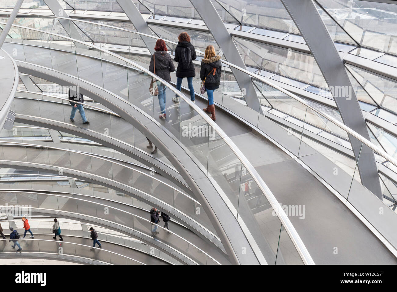 Several tourists walking at ramps inside the futuristic glass dome on top of the Reichstag (German parliament) building in Berlin, Germany. Stock Photo